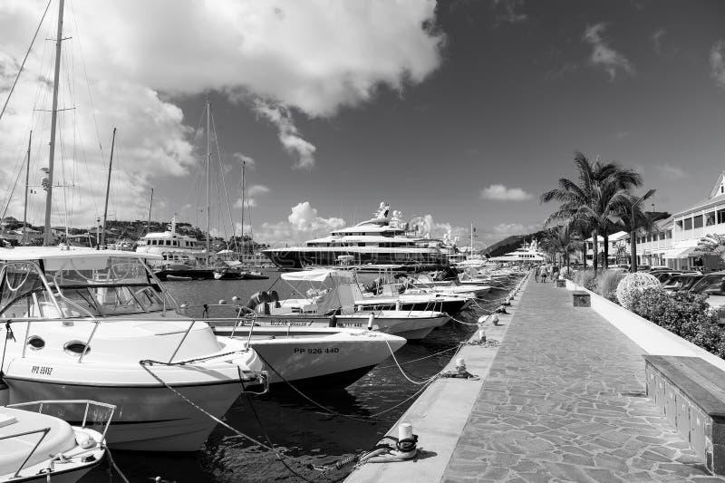 Gustavia stbarts - Januari 25, 2016: fartyg och yachter ankrade på havspir på den tropiska stranden Segling och segling royaltyfri foto