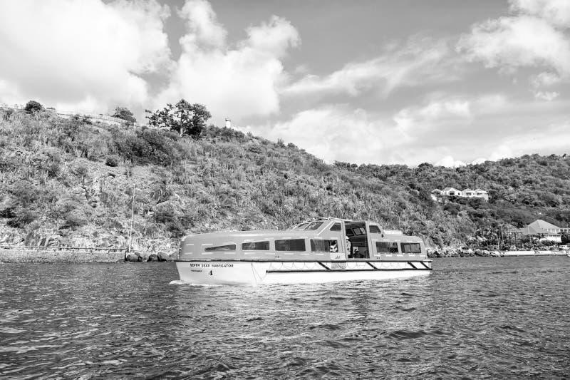 Gustavia, stbarts - 25 novembre 2015: viaggio della nave in mare blu lungo la spiaggia Trasporto e nave dell'acqua viaggiare immagine stock libera da diritti