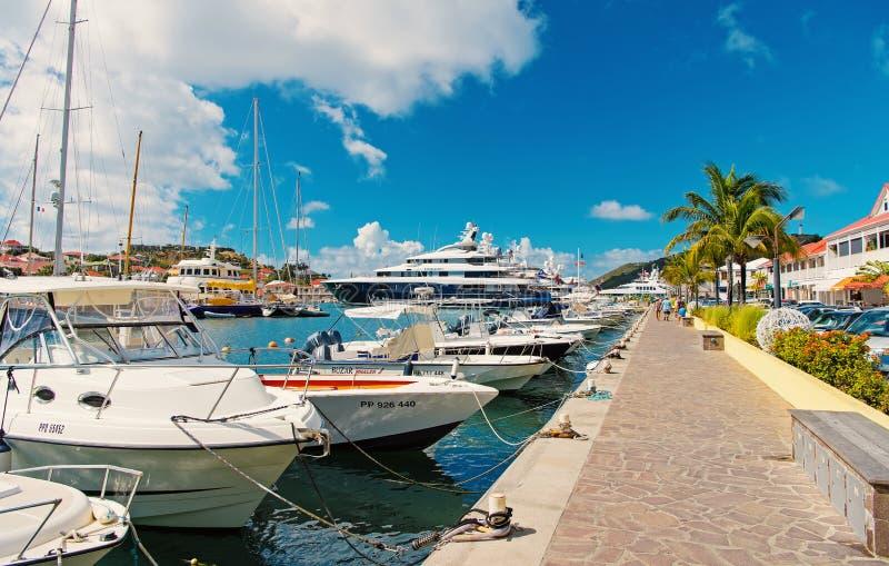 Gustavia, stbarts - 25-ое января 2016: шлюпки и яхты поставили на море пристань на якорь на тропическом пляже Плавать и плавать стоковая фотография