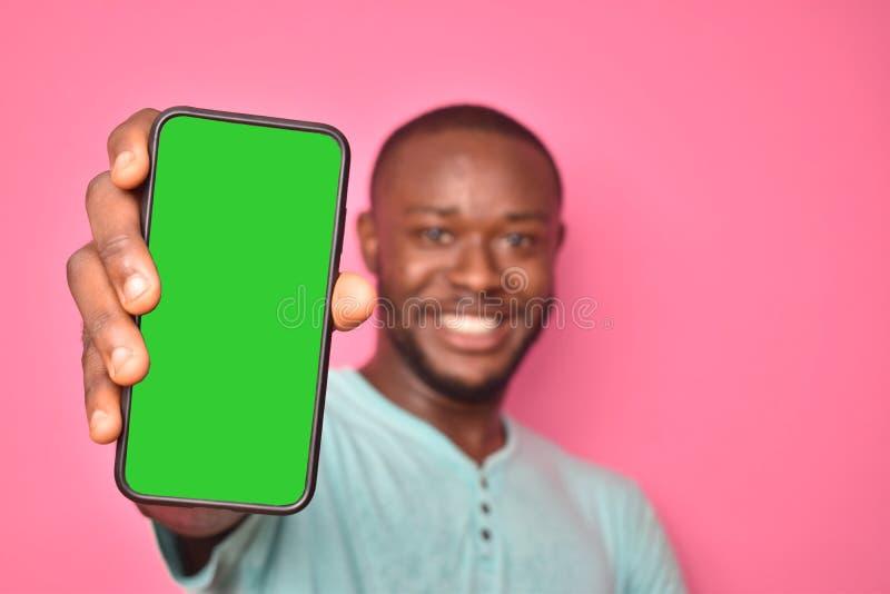 gut aufgeregter junger schwarzer Mann, der sich aufgeregt fühlt, während er seinen Bildschirm zeigt lizenzfreie stockfotos
