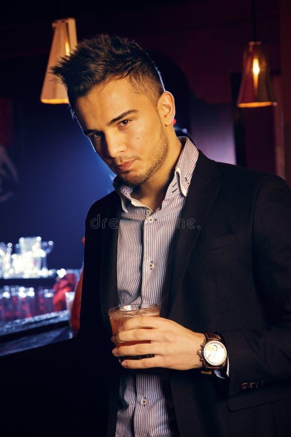 Gut aussehender Mann, der ein Glas Whisky hält stockfoto