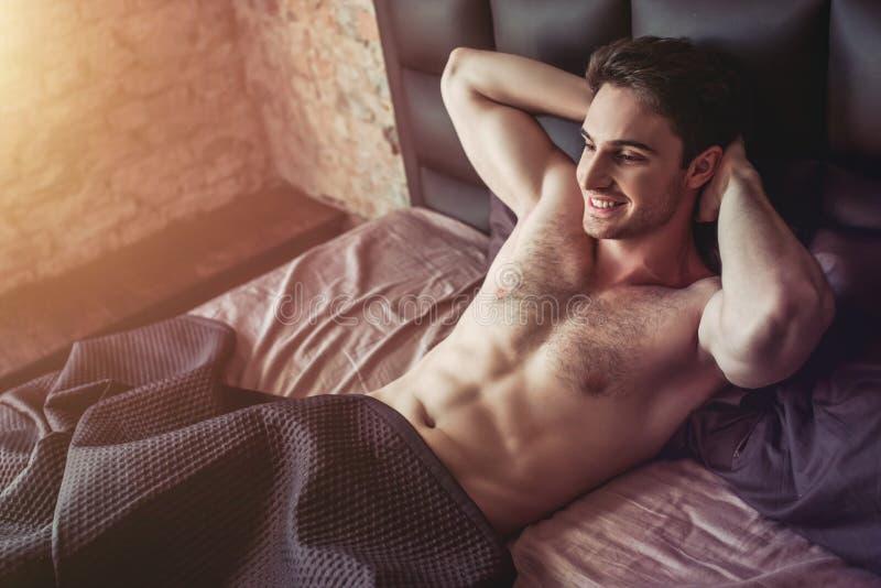Gut aussehender Mann auf Bett stockbilder
