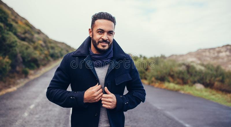Gut aussehender Mann auf ländlicher Landstraße an einem Wintertag lizenzfreie stockfotos