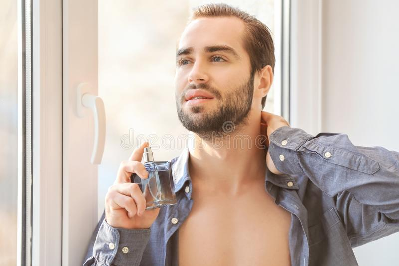 Gut aussehender Mann in aufgeknöpftem Hemd und mit Flasche lizenzfreie stockfotografie