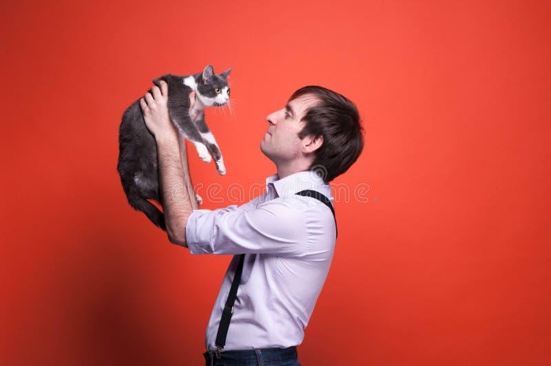 Gut aussehender Mann, der auf ausgestreckten Armen hält und nette graue und weiße Katze betrachtet stockbilder