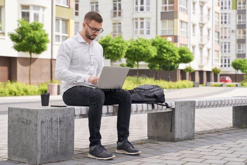 Gut aussehender Mann, der auf der Bank, draußen arbeitend an Laptop sitzt lizenzfreie stockfotografie