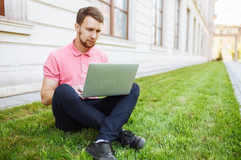 Gut aussehender Mann, der auf dem Gras in der Stadt mit einem Laptop, Jobsuche sitzt lizenzfreies stockbild
