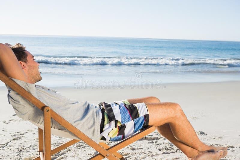 Gut aussehender Mann, der auf seinem bewundern Meer des Klappstuhls liegt stockfotos