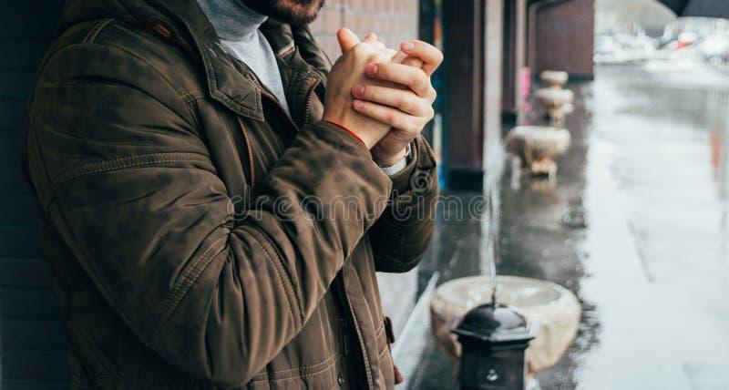 Gut aussehender Mann, der auf der Straße in der Winterzeit steht und seine Hände wärmt Kalter Tag es ` s Regnen Mann in der Jacke stockbilder