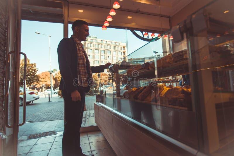 Gut aussehender Mann in der Bäckerei, eine Waffel beschließend, um zu essen lizenzfreie stockbilder
