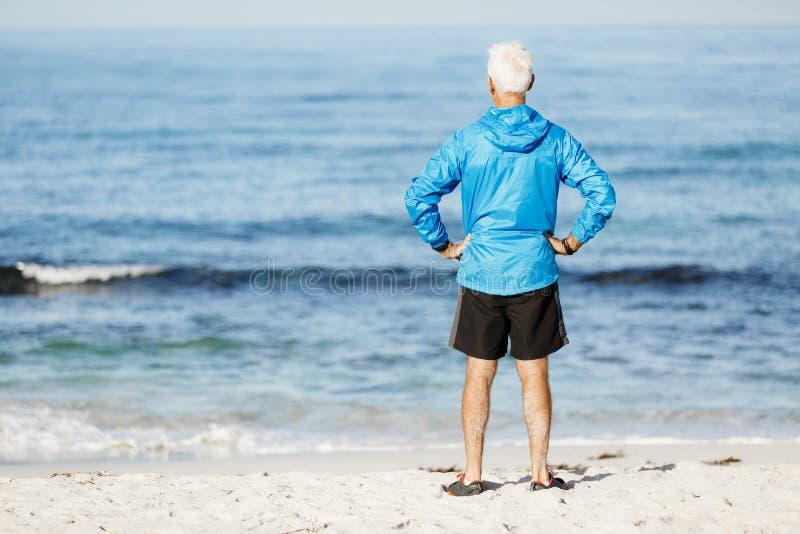 Gut aussehender Mann, der bei auf Strand allein stehen durchdacht schaut lizenzfreie stockbilder