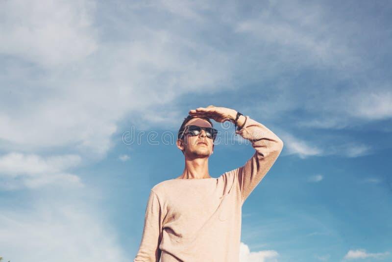 Gut aussehender Mann, der den Horizont mit einem blauen Himmel im Hintergrund betrachtet stockbild
