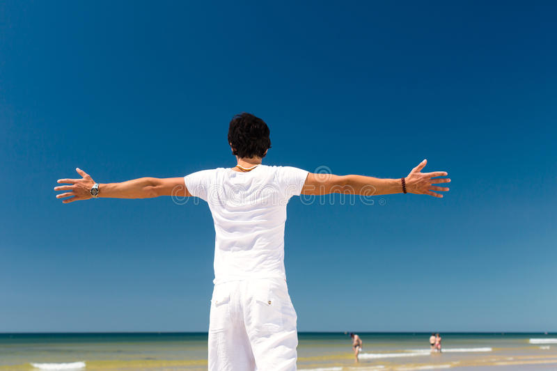 Gut aussehender Mann, der in der Sonne auf Strand steht stockfotografie