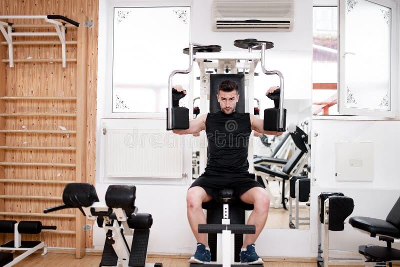 Gut aussehender Mann, der an der Turnhalle, tägliches Kastenübungsprogramm ausarbeitet stockbild