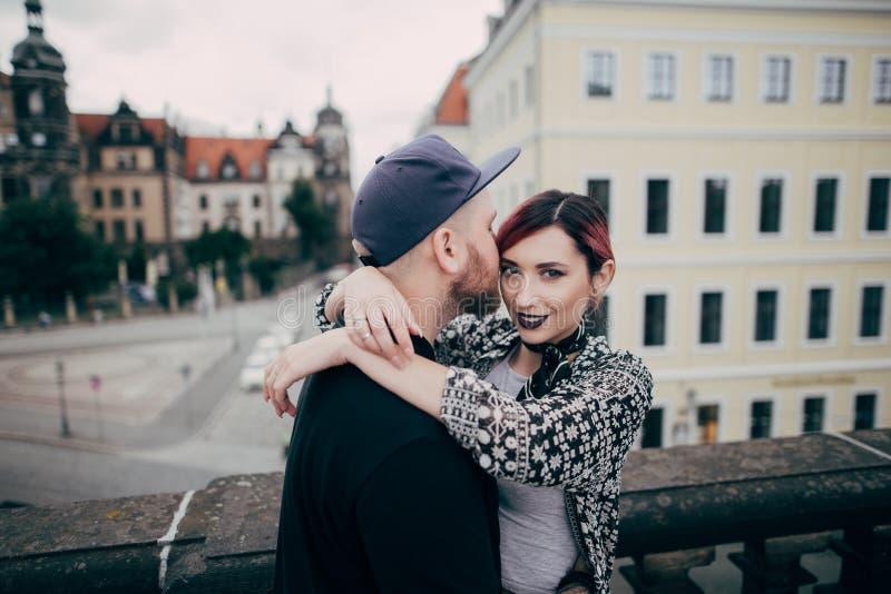gut aussehender Mann, der die schöne junge Frau betrachtet Kamera bei auf Brücke in Dresden zusammen stehen küsst stockfotos