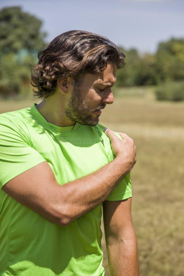 Gut aussehender Mann, der die Schulterschmerz während des Trainings hat lizenzfreie stockfotografie