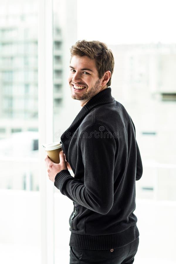 Gut aussehender Mann, der die Wegwerfschale schaut zurück zu Kamera hält lizenzfreie stockbilder