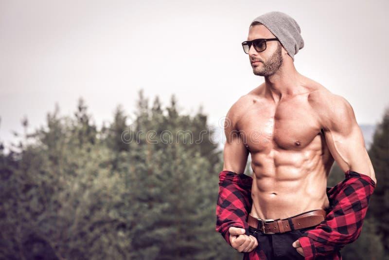 Gut aussehender Mann, der draußen überprüftes Hemd trägt stockfotos