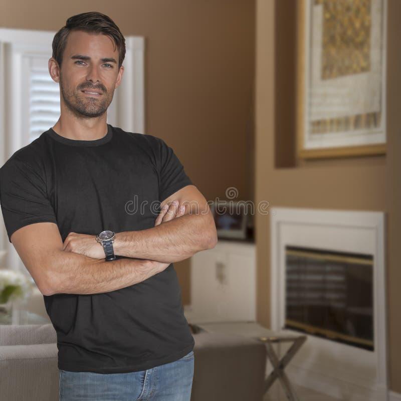 Gut aussehender Mann, der ein schwarzes T-Shirt und Jeansblicke an der Kamera trägt stockfotografie