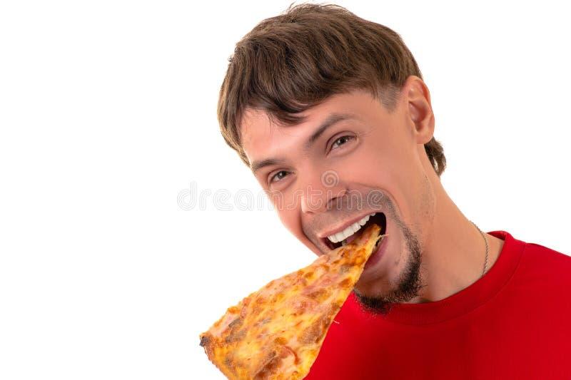 Gut aussehender Mann, der emotional Scheibenpizza isst stockfoto
