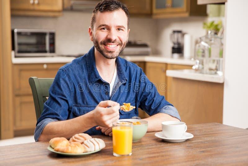 Gut aussehender Mann, der frühstückt stockbilder