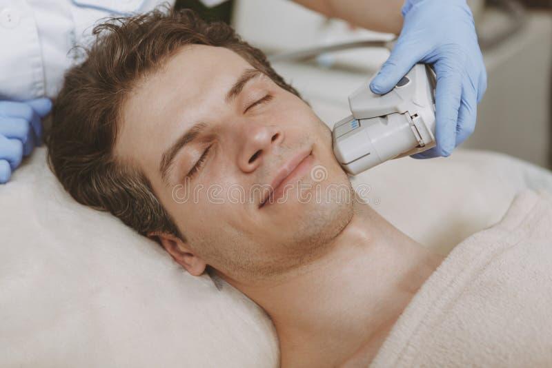 Gut aussehender Mann, der Gesichts-skincare Behandlung erh?lt lizenzfreie stockbilder