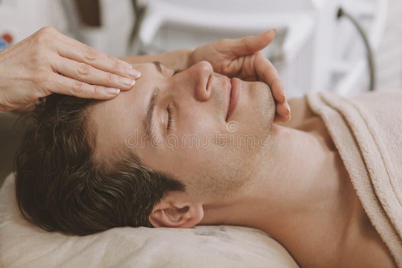 Gut aussehender Mann, der Gesichts-skincare Behandlung erh?lt stockbild
