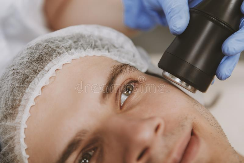 Gut aussehender Mann, der Gesichts-skincare Behandlung erh?lt stockfotografie