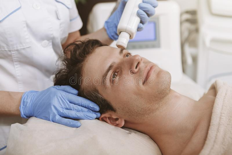Gut aussehender Mann, der Gesichts-skincare Behandlung erh?lt lizenzfreies stockbild
