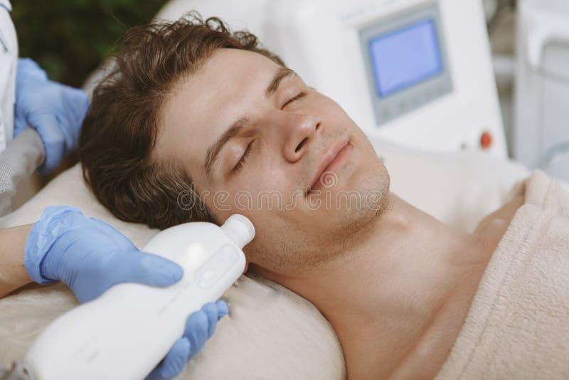 Gut aussehender Mann, der Gesichts-skincare Behandlung erh?lt lizenzfreie stockfotografie
