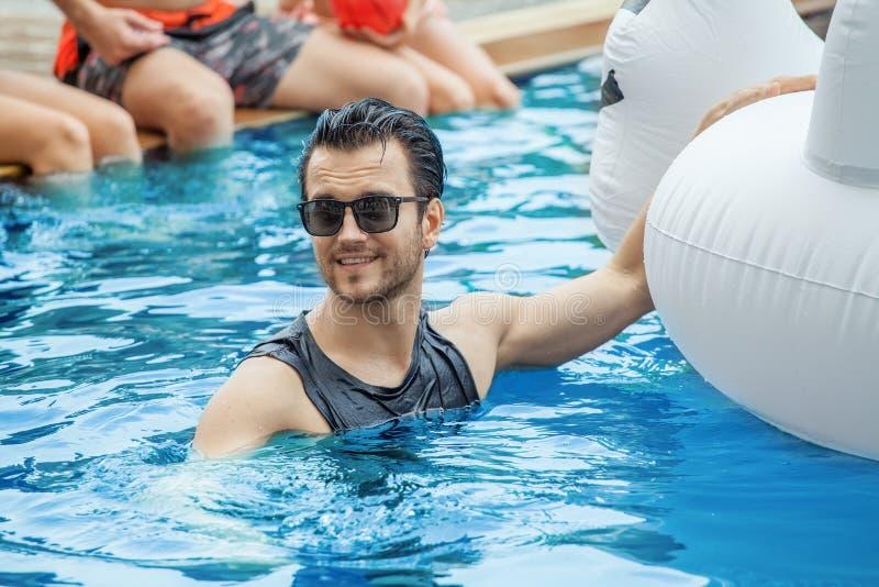Gut aussehender Mann in der Gruppe Freunden, die Partei im Pool mit i machen lizenzfreie stockfotos