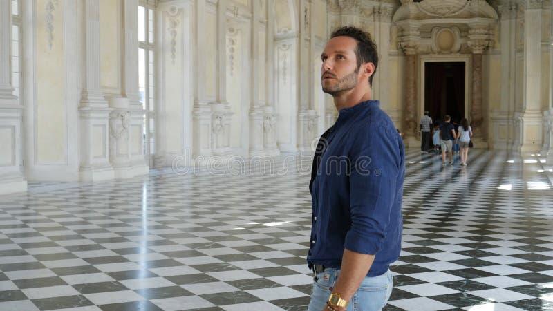 Gut aussehender Mann, der herum innerhalb eines Museums schaut stockfoto