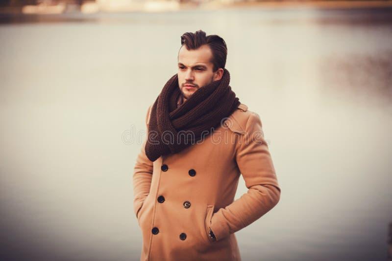 Gut aussehender Mann, der im Mantel aufwirft stockbild