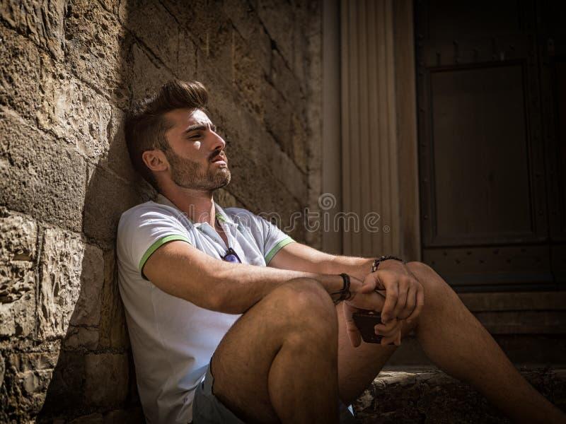 Gut aussehender Mann, der an der K?stenstadt sitzt lizenzfreie stockfotos