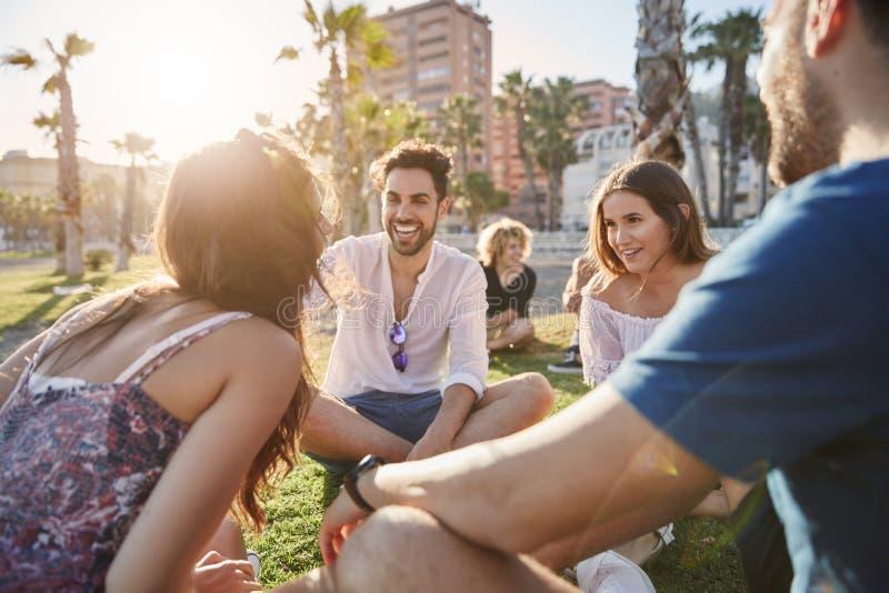 Gut aussehender Mann, der mit den Freunden draußen lachen sitzt lizenzfreie stockfotos