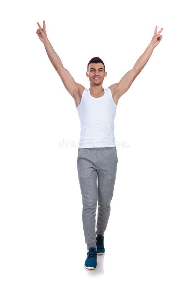 Gut aussehender Mann, der mit den Händen in der Luft tritt und feiert lizenzfreie stockfotografie
