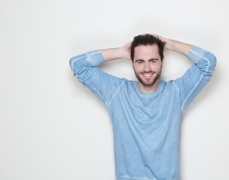 Gut aussehender Mann, der mit der Hand im Haar lächelt stockbilder