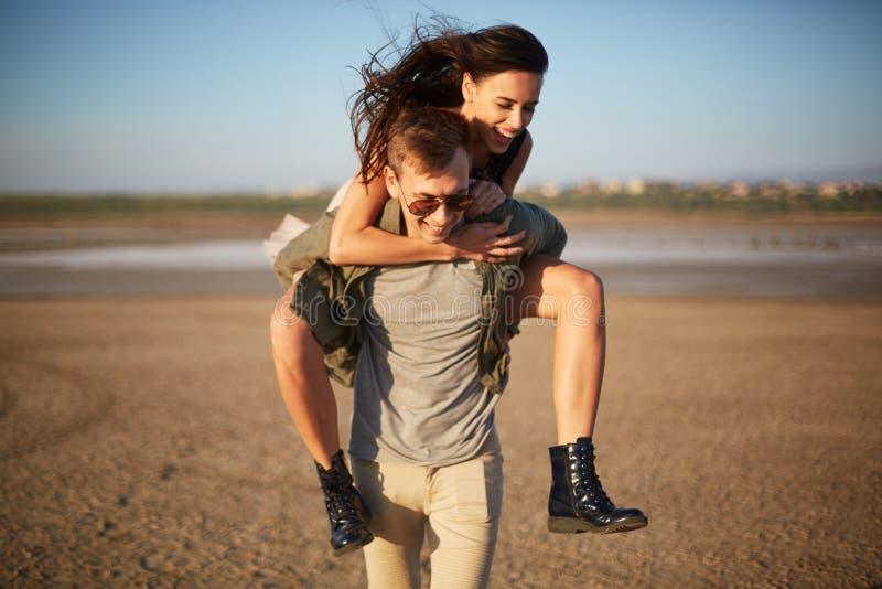 Gut aussehender Mann, der mit hübschem Mädchen auf einer Rückseite auf einem natürlichen Hintergrund geht Romantisches Reisekonze lizenzfreies stockbild