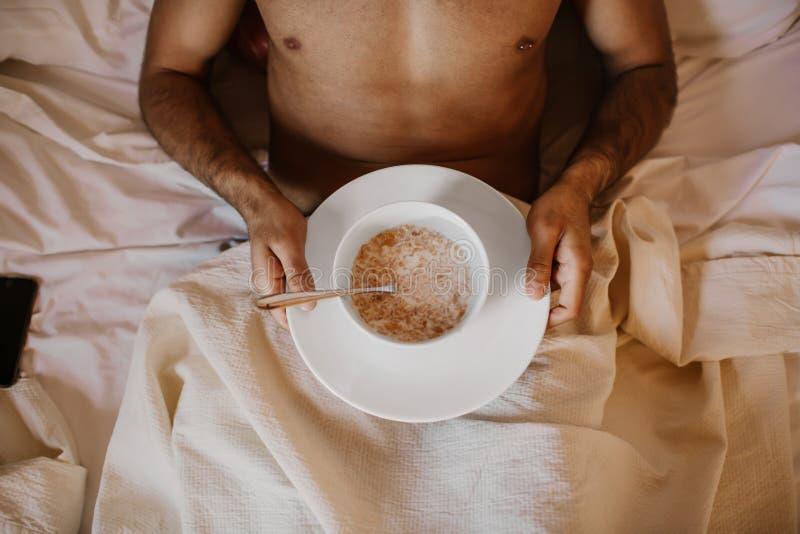 Gut aussehender Mann, der morgens auf Bett mit gesundem Frühstück liegt Attraktiver Kerl, der zu Hause im Schlafzimmer, sexy Jung stockfotos