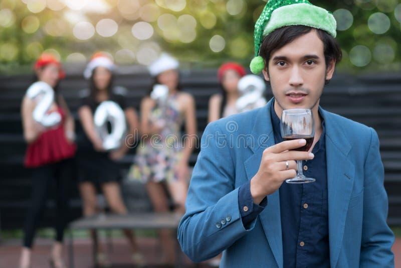 Gut aussehender Mann, der Sankt Hüte mit Holdingglas Wein an trägt lizenzfreies stockfoto