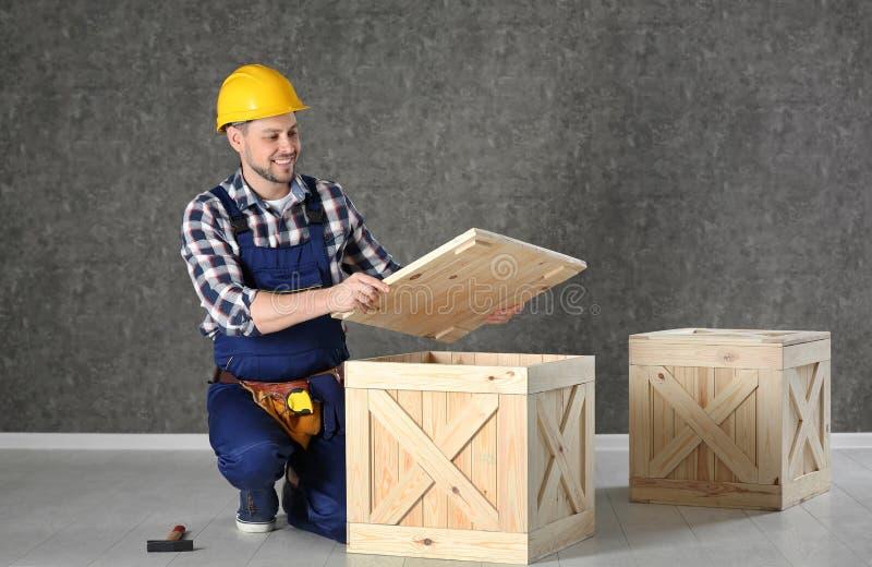 Gut aussehender Mann in der Schutzhelmfunktion mit hölzerner Kiste lizenzfreies stockbild