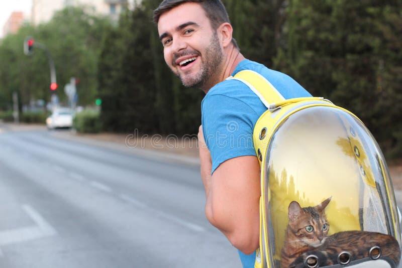 Gut aussehender Mann, der seine Katze im transparenten Rucksack trägt stockbilder