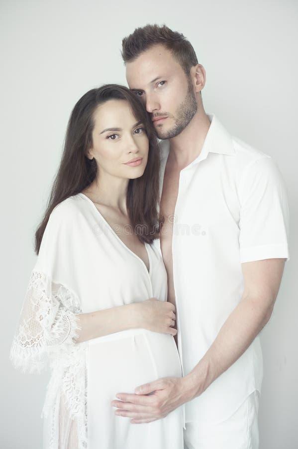 Gut aussehender Mann, der seine schwangere Frau umarmt lizenzfreie stockfotografie