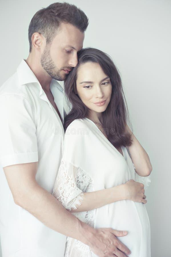 Gut aussehender Mann, der seine schwangere Frau umarmt stockfotografie