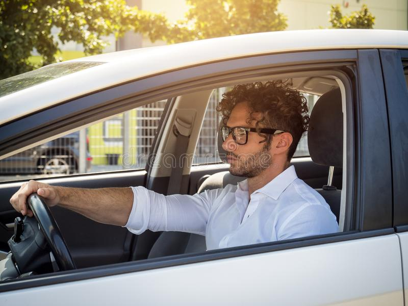 Gut aussehender Mann, der in seinem Auto, weg schauend sitzt stockfotografie