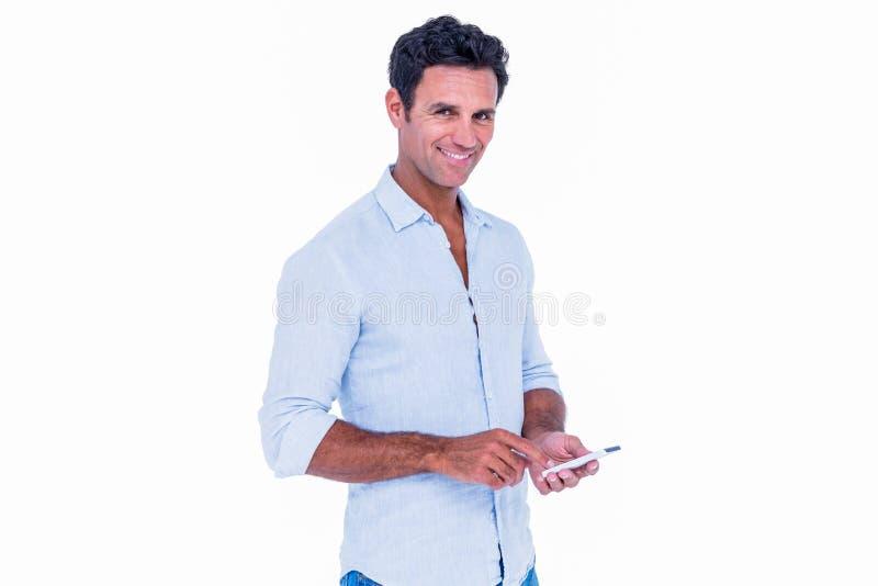 Gut aussehender Mann, der seinen Smartphone verwendet stockfoto