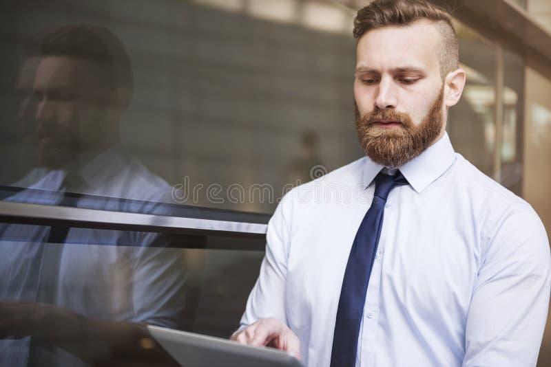 Gut aussehender Mann, der Tablette verwendet stockfotografie