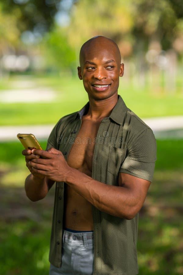 Gut aussehender Mann, der Text auf seinem Smartphone sendet und über seiner Schulter flüchtig blickt stockfoto