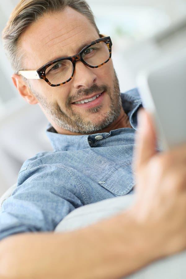 Gut aussehender Mann, der tragende Brillen der Tablette verwendet stockfoto