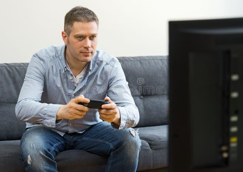 Gut aussehender Mann, der Videospiel spielt stockfotos